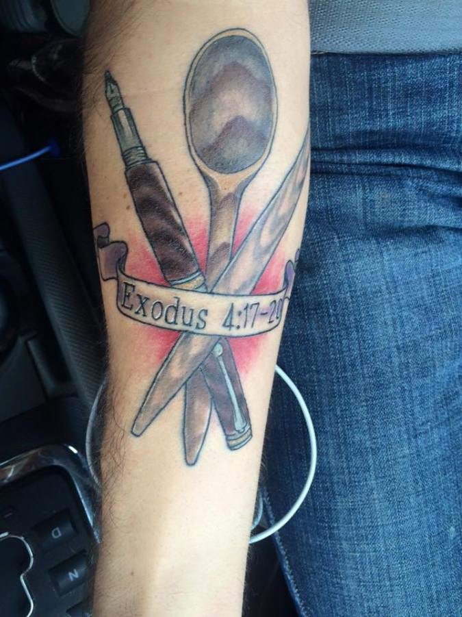 "A picture of the authors first tattoo, depicting a wooden spoon, a rolling pin, and a fountain pen with a banner reading ""Exodus 4:17-20"