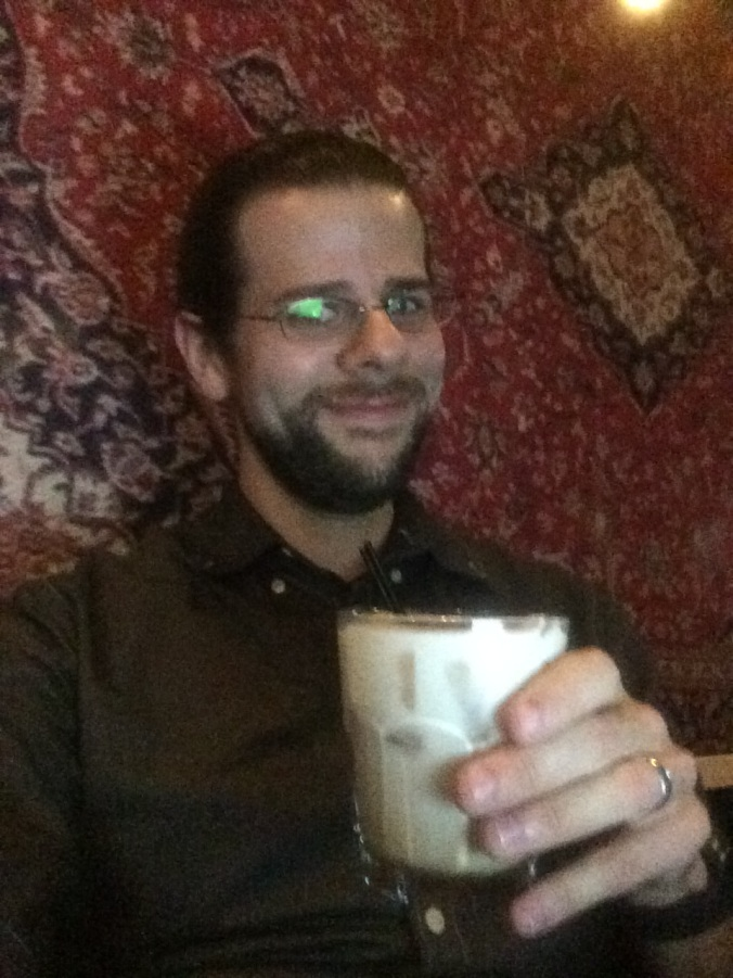 The author enjoys a White Russian cocktail in front of the rug.