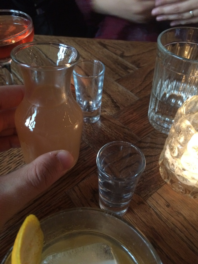 Small carafe of cloudy pink brine with two shot glasses in the background