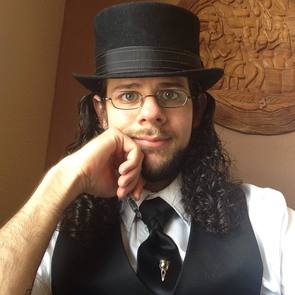Self-portait of the author in a black top hat, tie, and vest. Holding a fountain pen.