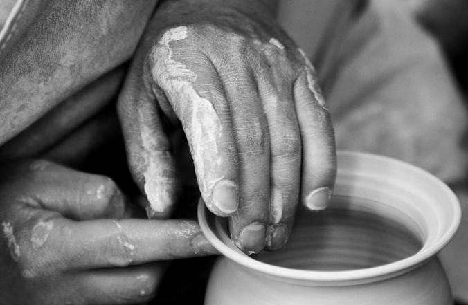 close up of hands making a clay pot