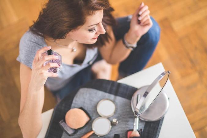 Young woman applying makeup and perfume