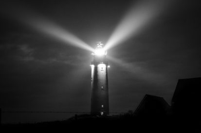 A gray scale photo of a lighthouse at night, with light shining in all directions.