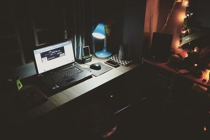 a dark empty office illuminated by a desk lamp and computer
