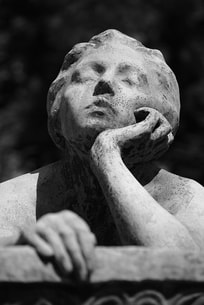 A marble statue of a female figure with her chin in her palm
