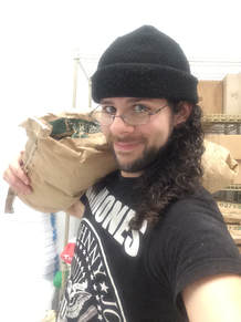 The author holding a flour sack on his shoulder while smiling, wearing a black knit cap and a Ramones tshirt.