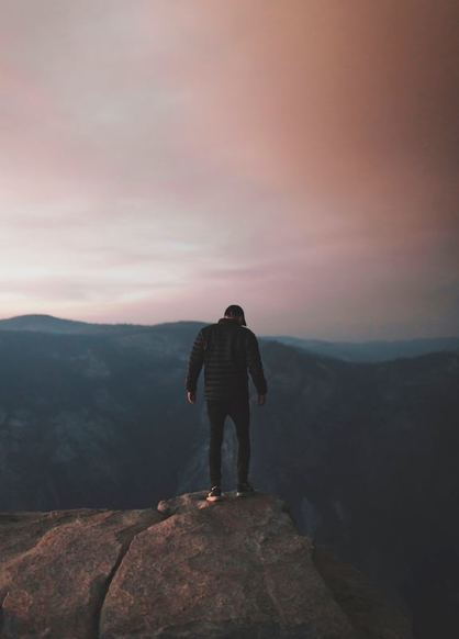Man standing on top of a mountain at dusk in Yosemite