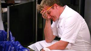 Chef Gordon Ramsay looking exhausting, holding his forehead