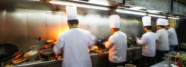 A busy line in a restaurant kitchen. Five cooks working with their backs to the camera.