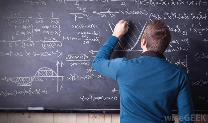 Teacher writing equations on chalkboard