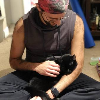 The author in exercise clothing with his cat curled up in his lap.