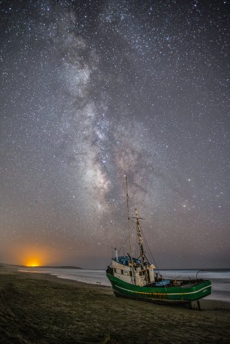 A beached fishing boat at dusk under the Milky Way