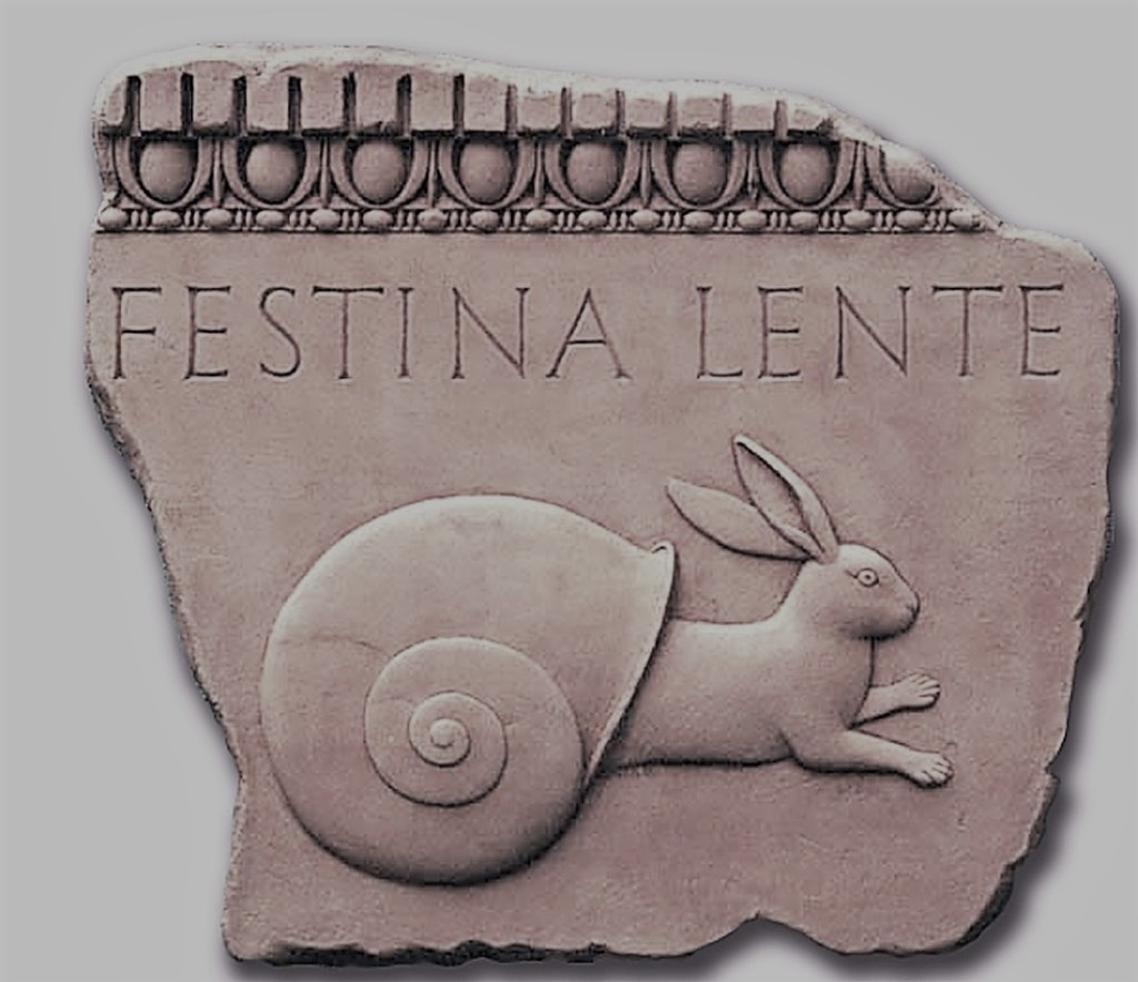 """Relief carving of a rabbit coming out of a snails shell with the words """"Festina Lente"""" written above it"""