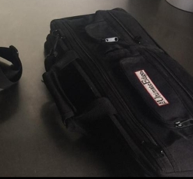 A black messenger bag and a black knife roll on a steel table with knives in the background.
