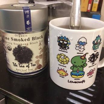 "Close-up of a mug of tea. The mug has Cthulhu gods designed like Sanrio characters on it, and next to the mug is a tin of Tao of Tea's ""Pine Smoked Black"" lapsang souchong tea."