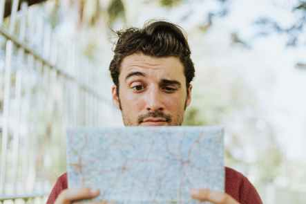 A man looking at a map, confused
