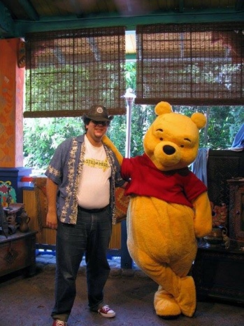 An old picture of the author, standing next to Winnie the Pooh