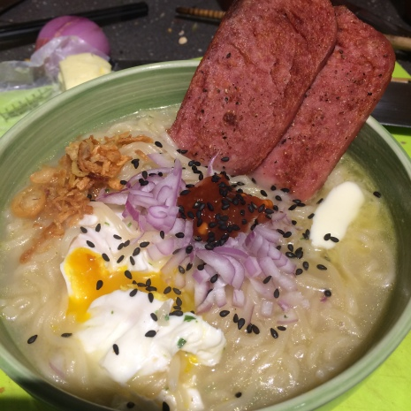 Homemade Tonkatsu Ramen bowl with poached egg, chili paste, shallots, fried onions, and grilled Spam.