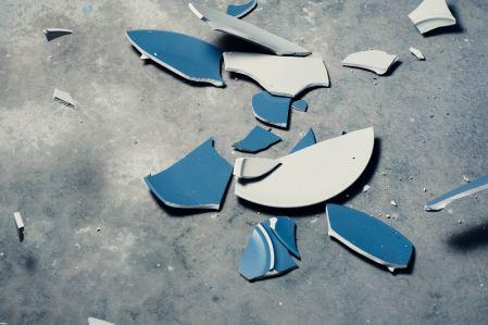 Broken blue plates on cement