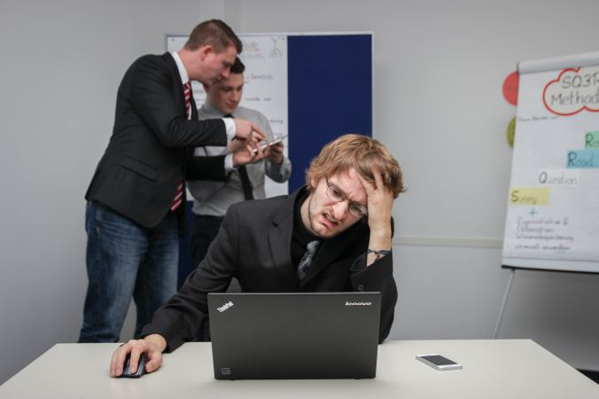 stressed out man grimacing at a black laptop while two other men talk behind him