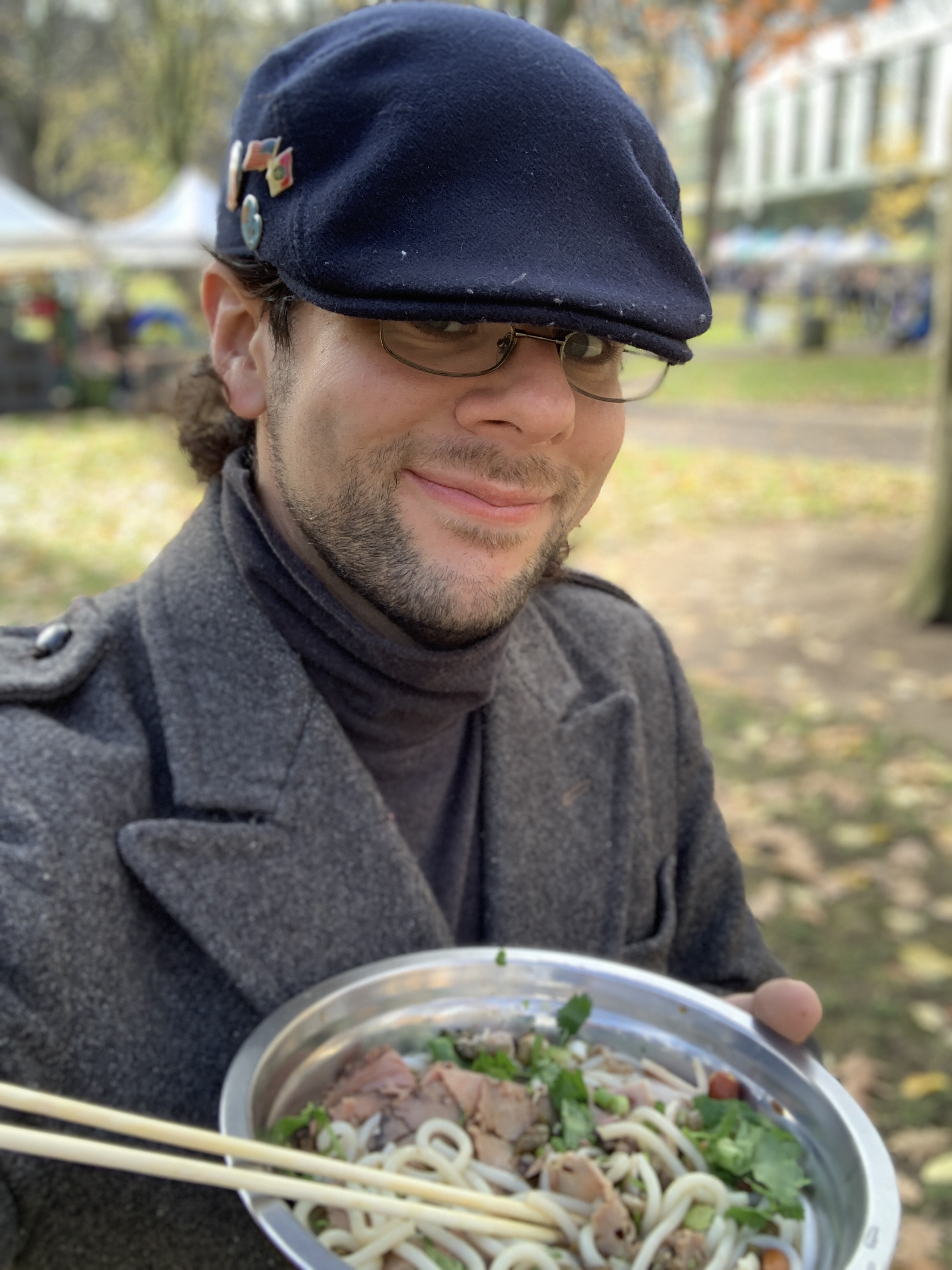 Selfie of the author in a gray wool coat and blue cap, holding up a bowl of noodle soup with chopsticks. It is outside  on a fall day.