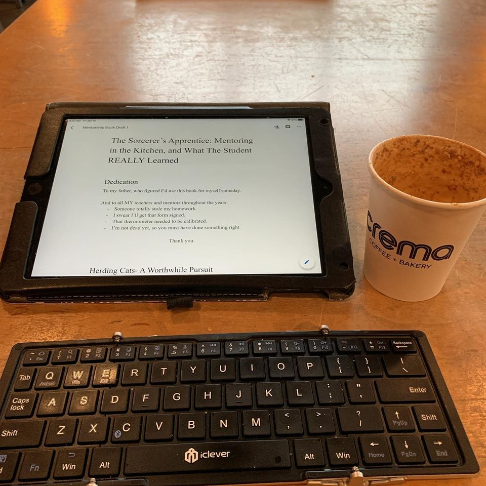 The author's ipad and folding keyboard next to a seemingly empty coffee cup.