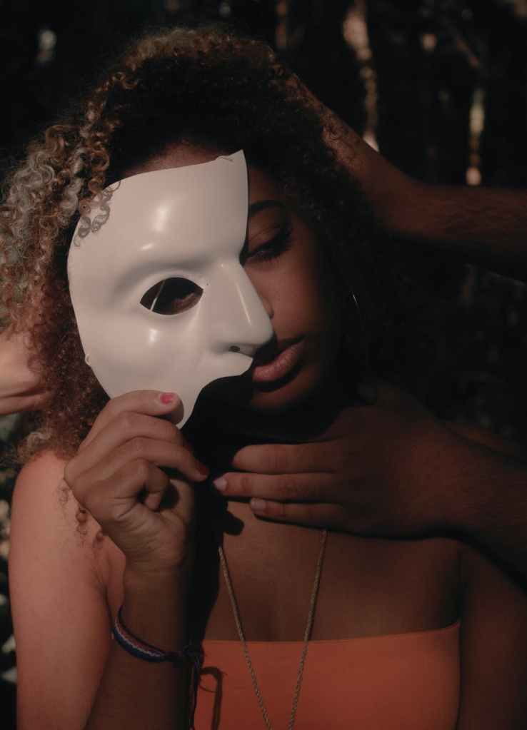 A young woman partially covering her face with a demi-mask in her right hand.