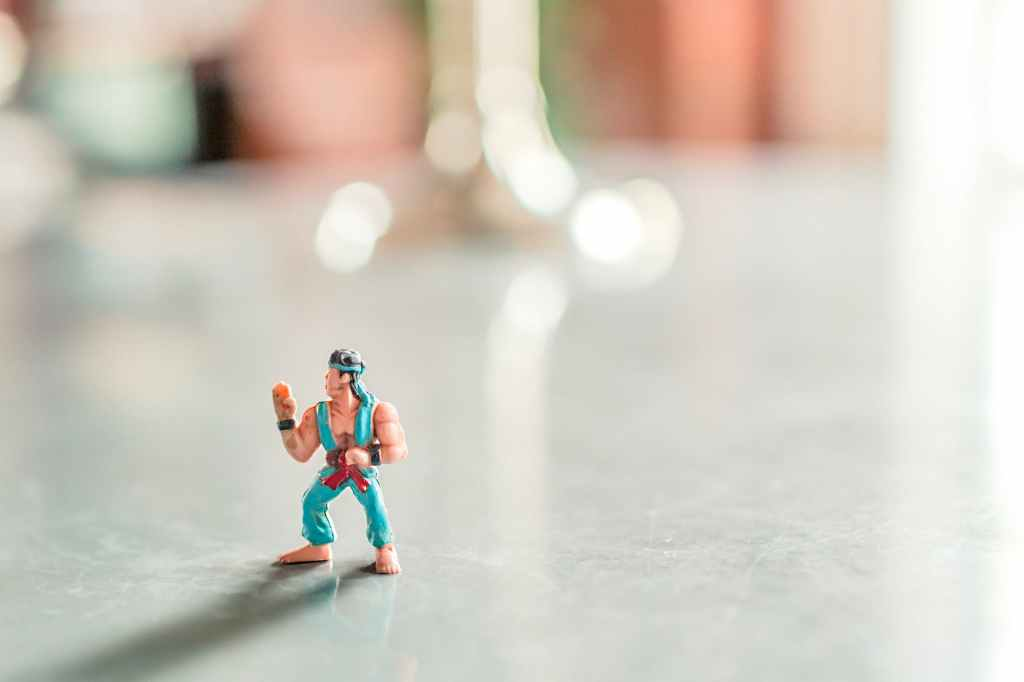 Close-up shot of a small action figure in a karate uniform on an empty table.