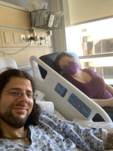 Selfie of the author and his wife. Matt is in a hospital bed and gown, his wife sitting beside him in a chair with  mask on.