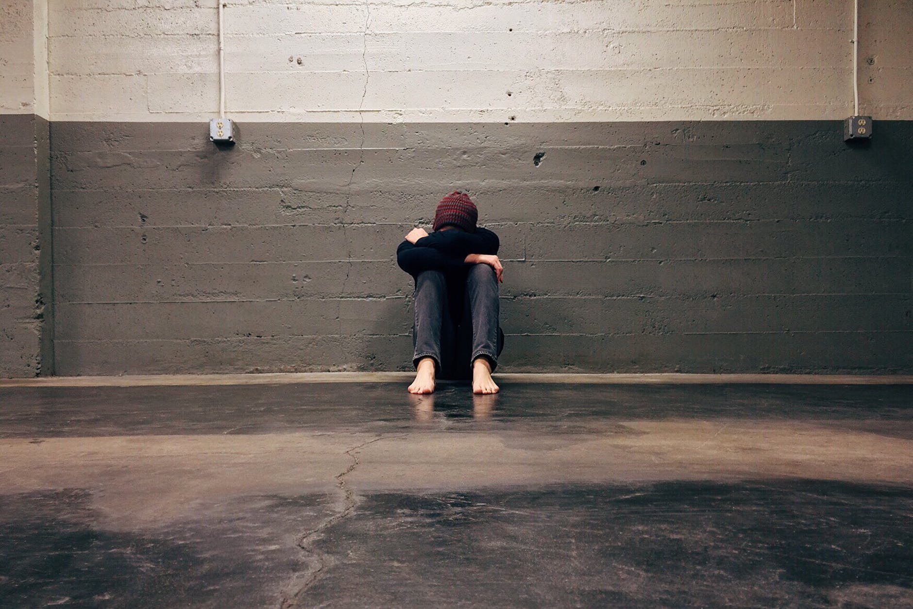 A person sits against a concrete wall with their arms on their knees and their head down. They are barefoot on a concrete floor.