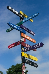 A multicolored sign post pointing to directions around the globe.