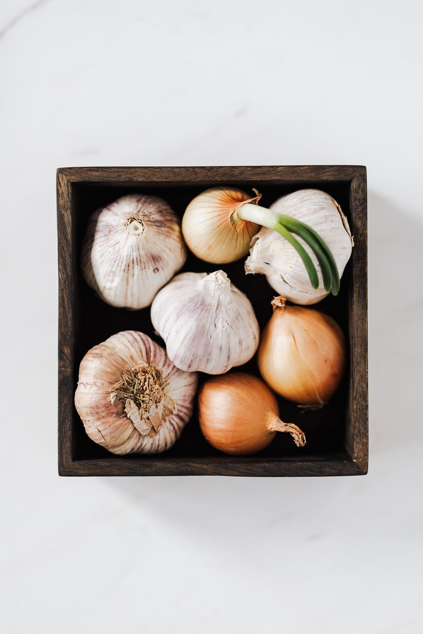 An overheard picture of a box full of garlic and onions on white marble table.