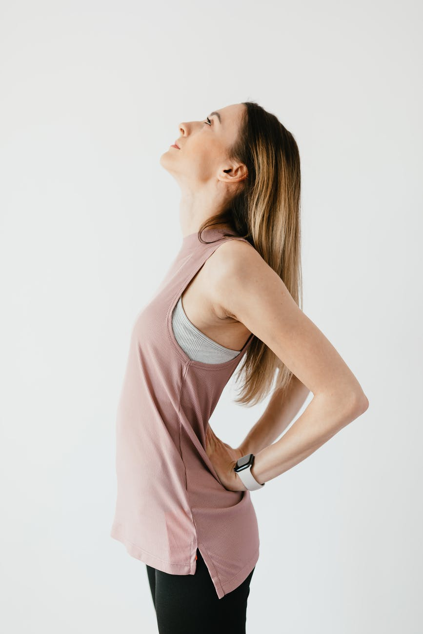 A young white woman stands up straight in workout attire, a placid expression on her face in profile with her face tilted up to the ceiling of a blank room