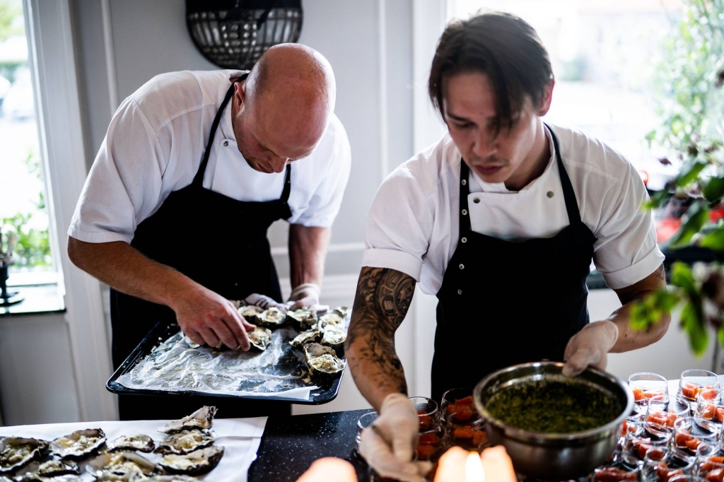 Two cooks wearing black aprons in a white room prepare an oyster bar