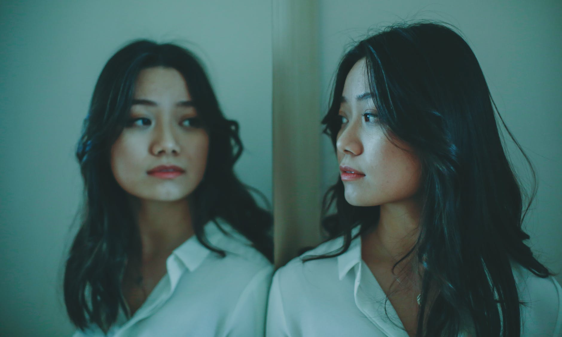 A young Asian woman in a white shirt looking at herself sideways in a mirror