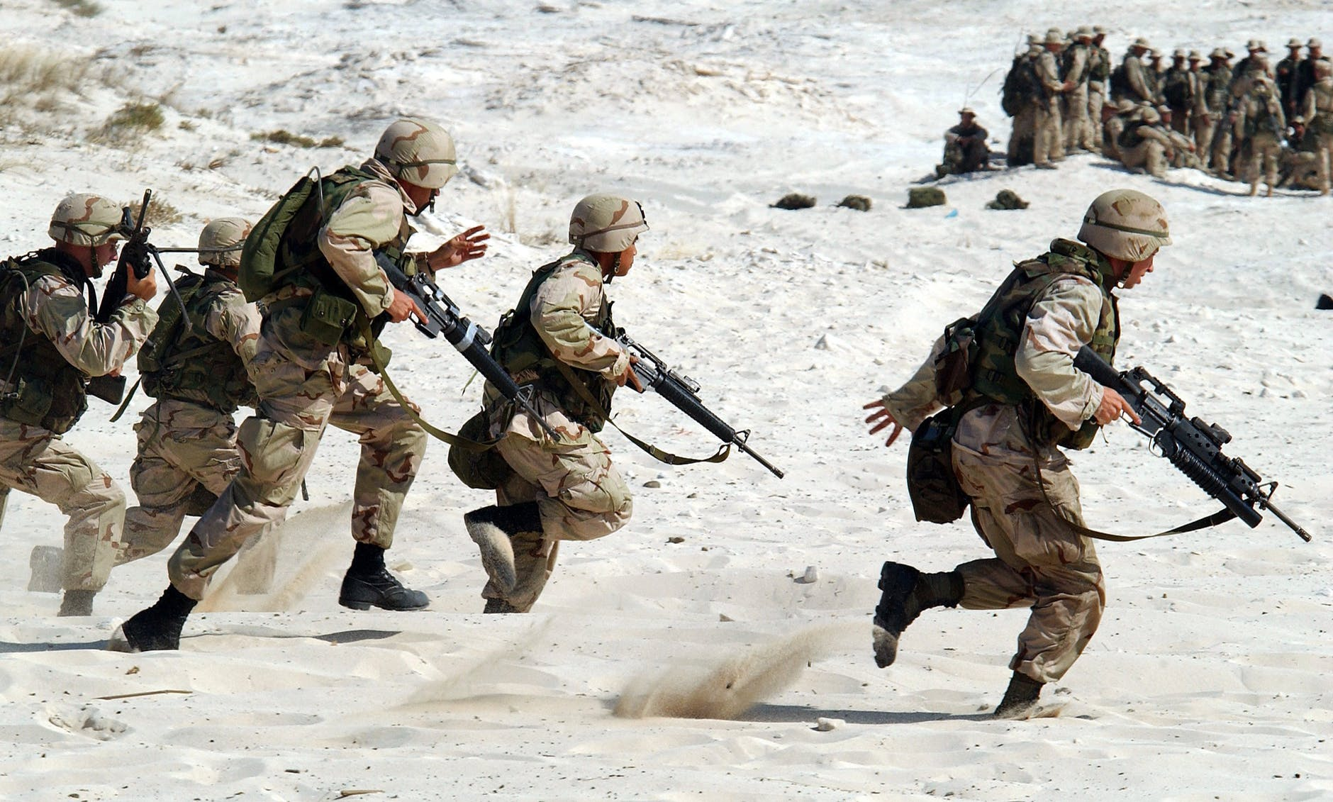 Action shot of five American soldiers running across a desert landscape