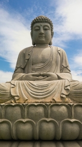 A giant statue of the Buddha seated on a lotus platform against a blue sky