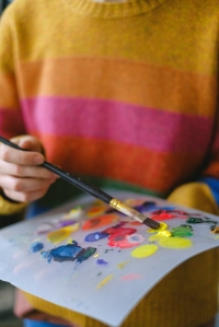 Picture of someone in a striped sweater mixing paints on an artist's pallet.