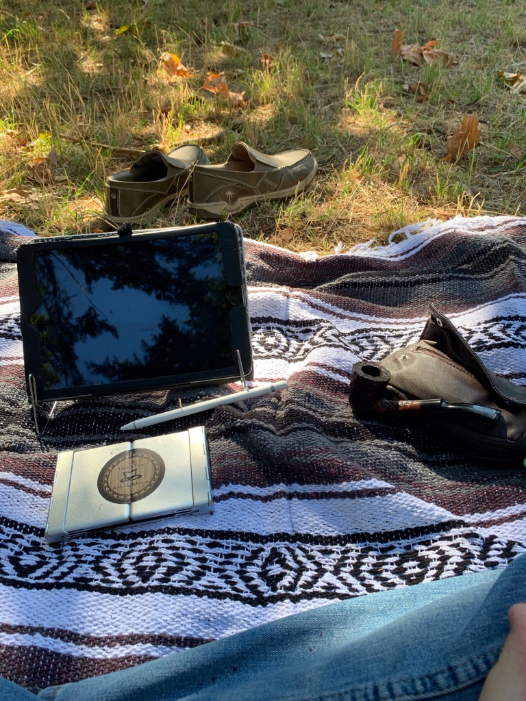 A striped Mexican blanket is on a grassy field. On the blanks are a pair of loafers, an ipad, a folding keyboard, and a tobacco pipe.