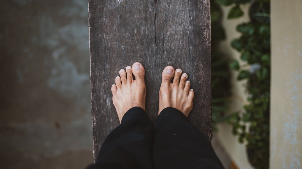 A pair of bare feet on a narrow plank. Either side indicates the person is standing at a great height.