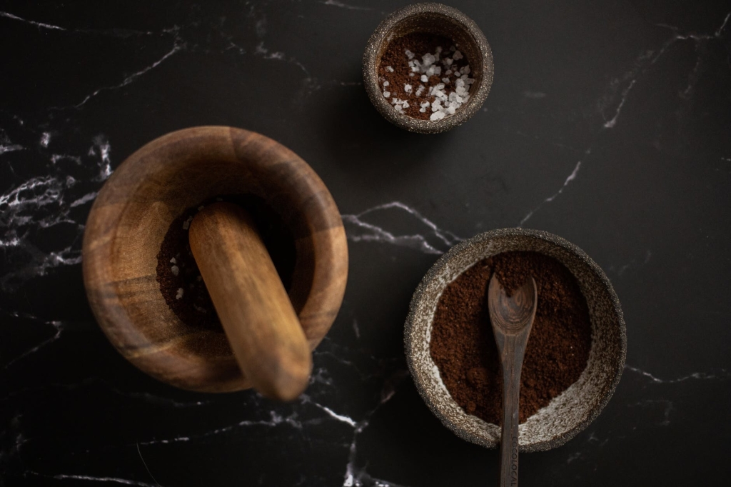 A wooden mortar and pestle with two spice bowlss on a black slate tabletop.